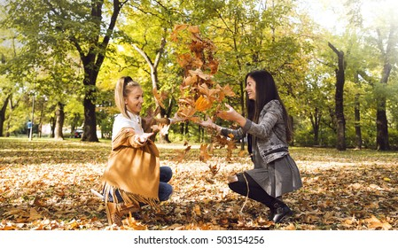 Two girls in the park throwing leaves.
