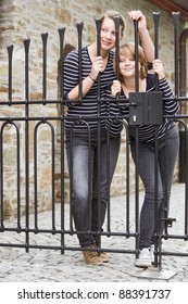Two girls peeking through closed gate