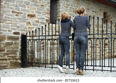 Two girls peeking through gate, rear view