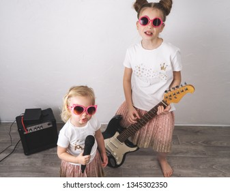 Two girls in pink sunglasses and identical T-shirts sing with a microphone and play the electric guitar.