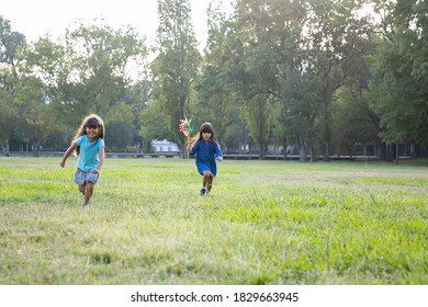 Two girls with pinwheels running to camera on grass, having race in park. Front view, full length. Children outdoor activity concept