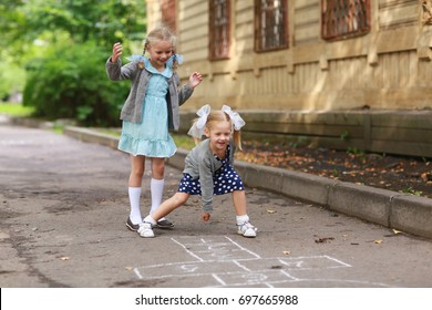Two girls play in the courtyard in the classics. The concept of a fun children's summer vacation