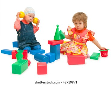 Two girls play cubes on a white background