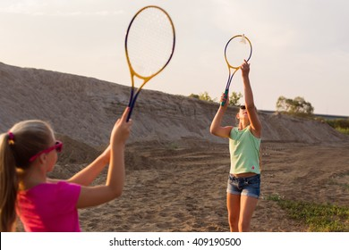 two girls playing badminton outdoor