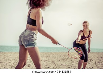 two girls playing beach badminton. best friends of multicultural origin having fun with badminton racket and shuttlecock. concept of diversity people leisure and active beach holidays