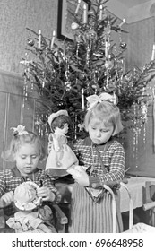 Two girls playing with dolls by Christmas tree