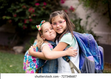 Two girls are playing excitedly and anxiously before their first day of school.