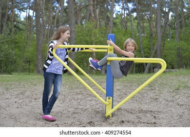 Two girls are playing on the playground on the yellow metal attraction. It's windy. The pine trees are all around.