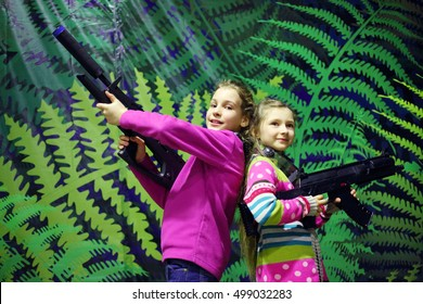 Two girls pose together with big machine guns near wall, lasertag game