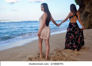 Two girls posing on the beach in front of the rock. at dawn
