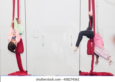Two girls practicing circus class with red silk