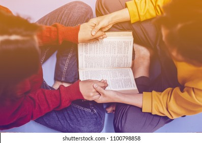 two girls are praying together over holy bible with the light from above with copy space for your text