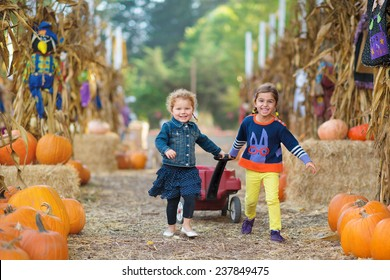 Two Girls Pulling a Wheelbarrow at Pumpkin Patch