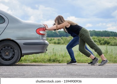 Two girls pushing their car which has run out of petrol along a country road in summer day