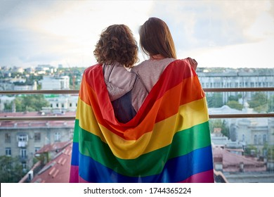 Two girls with rainbow flag looking out the window at the city. Lesbian couple celebrating pride month during Covid-19 quarantine, stay at home
