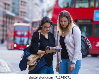 Two girls read a map in the city center of London