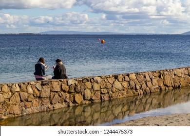 Two girls reading in Blackrock Beach in Salthill, Galway, Ireland