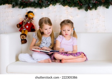 two girls reading a book in the Christmas decorations