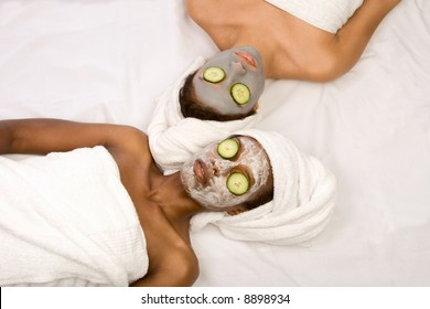 Two girls are relaxing during facial mask application in spa