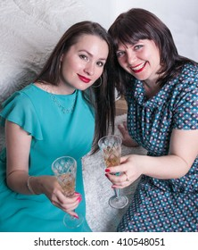 Two girls relaxing with a glass of champagne