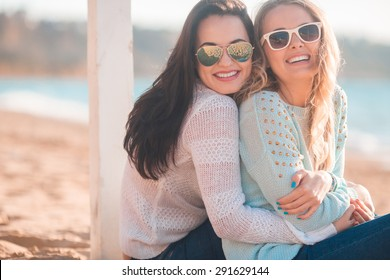 Two girls resting on the autumn beach