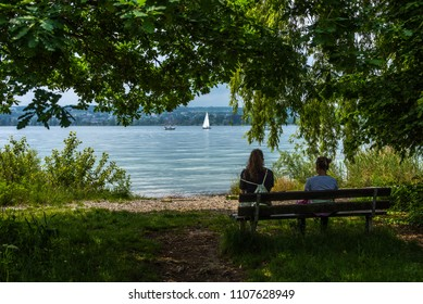 Two girls resting on a shady bench enjoying the views over lake constance on a sunny spring day.
