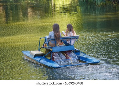 Two girls ride on catamaran on the lake. Vacation