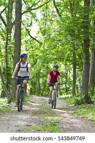 two girls riding the bicycle in the forest