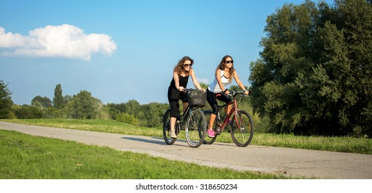 Two girls riding bikes on a path in a park.
