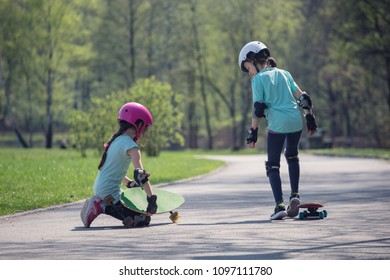 Two girls riding on skateboards.