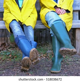 Two girls with rubber boots on a rainy day