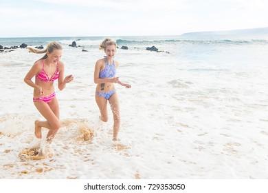 Two girls running on ocean beach