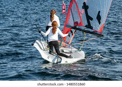 Two Girls Sailing small sailboat with long red hair viewed closeup from behind. Teamwork by junior sailors racing on saltwater Lake Macquarie. Photo for commercial use.