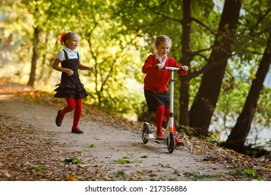 Two  girls in school uniform playing in the park and riding on scooter