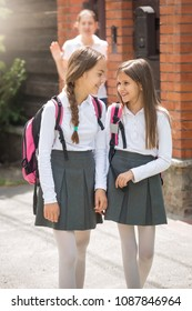 Two girls in school uniform talking while leaving to school