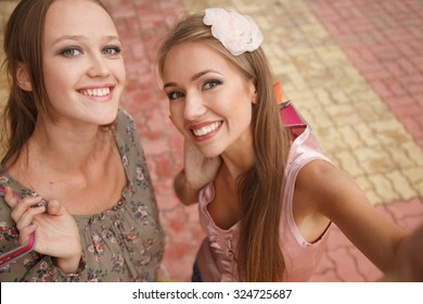 Two girls with shopping bags are taking pictures of themselves. High angle view. Shoot looks like selfie