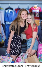 Two girls with shopping are hugging each other in the store