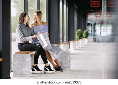 Two girls with shopping sitting on a bench in the Mall