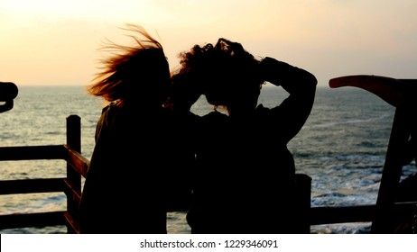 two girls siluettes in sunset at sea freedom friendship