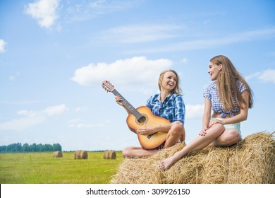 Two girls are sing in full length on straw bale Couple of girlfriends on country vacations are sitting on farm stack of dry thatch Nice hot summer day Young adult woman with slim sexy legs