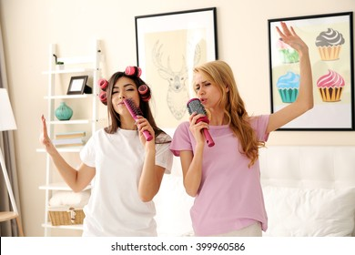 Two girls singing with combs on a bed in living room