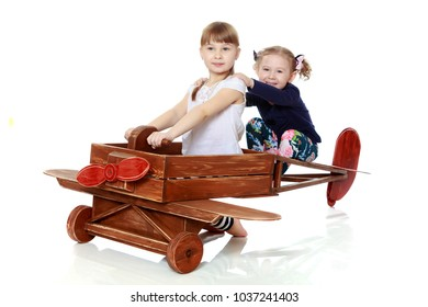Two girls sister play with a wooden plane. The concept of a happy childhood, playing in the family. Isolated on white background.
