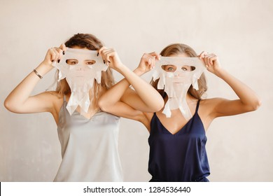 Two girls sisterhood, isolated background, in silk tops posing, having fun moisturizing fabric face masks. Concept skin care