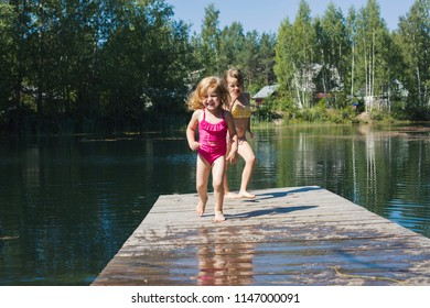 Two girls sisters are playing on the wooden pier at the lake
