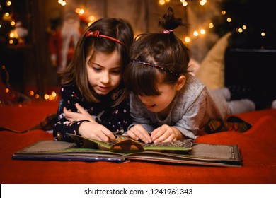 Two girls sisters reading book on floor  in Cristmas environment with light background
