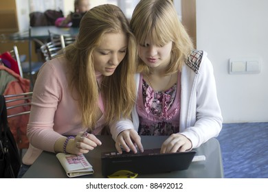 Two girls sit before the notebook and discuss something