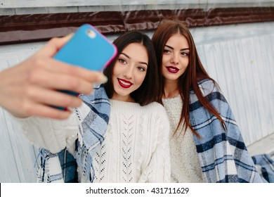 Two girls sit on the bench and do selfie