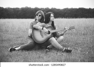 Two girls sit on the grass and play the guitar. Black and white