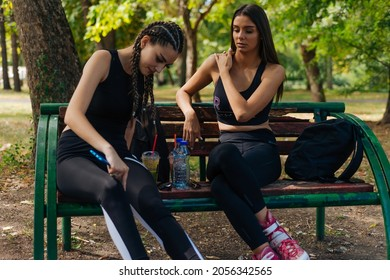 Two girls sit in a park while taking a break from rollerskating drinking smoothie,water and gossiping. Girls bonding concept.