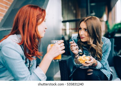Two girls sitting in a bar having fruit salad and juice talking - best friends, chatting, gossip concept